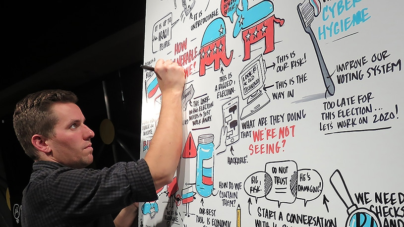 One of Ink Factory's artists graphic records a political talk at Chicago Ideas