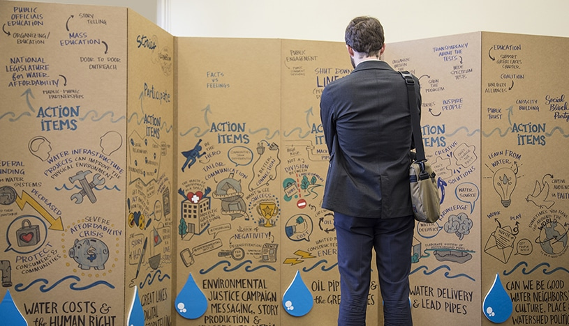 An attendee to the Freshwater Lab summit in Chicago studies a mural created by Ink Factory