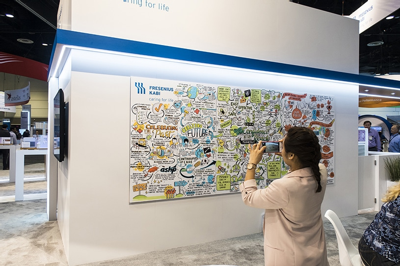 A conference attendee snaps a photo of Ink Factory's visual notes at the Fresenius Kabi trade show booth