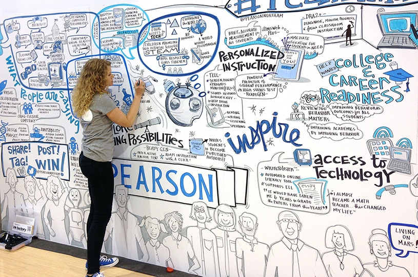 An artist from Ink Factory draws live on a trade show booth for Pearson